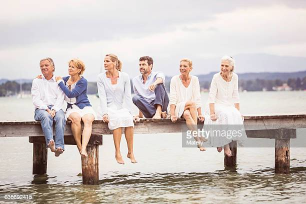 group of friends, sitting in row on edge of pier - mittelgroße personengruppe stock-fotos und bilder