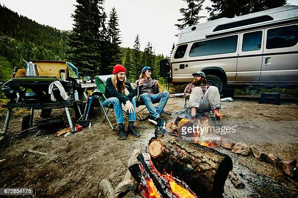 Group of friends sitting near fire while camping