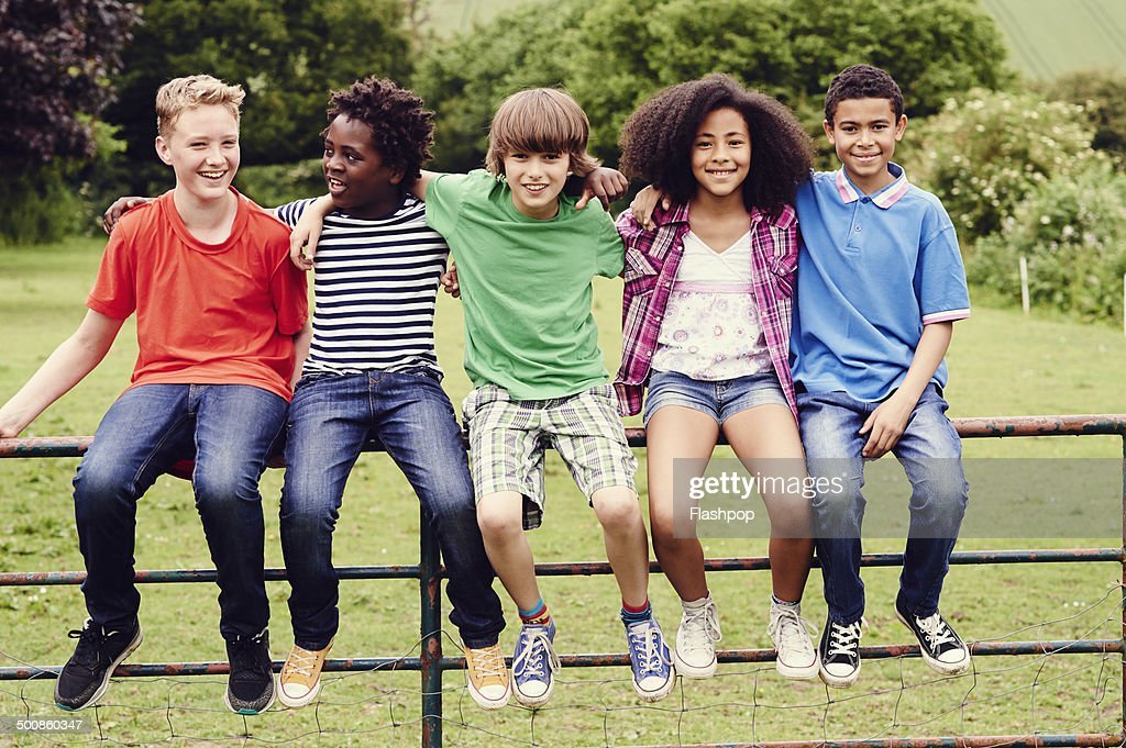 Group of friends sitting on a gate in a field : Stock Photo