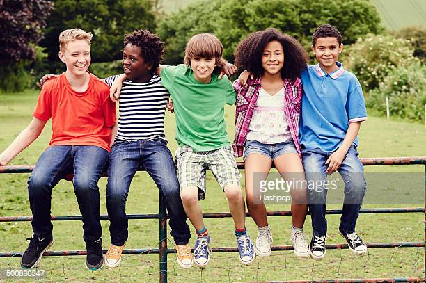 group of friends sitting on a gate in a field - pre adolescent child stock pictures, royalty-free photos & images