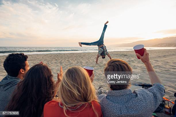 Group of friends sitting on beach, watching friend do cartwheels on and, sunset, rear view