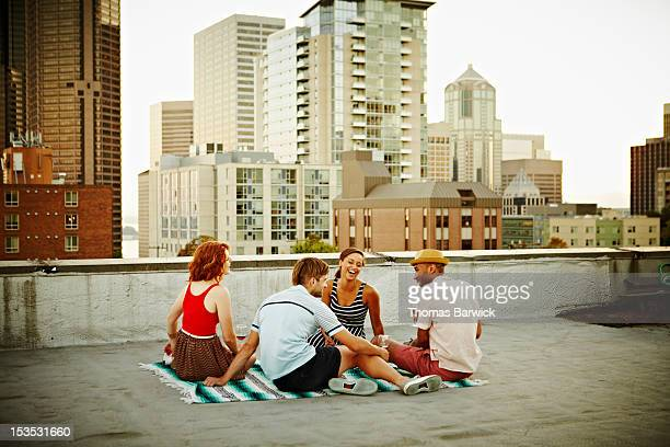 Group of friends sitting on blanket on rooftop