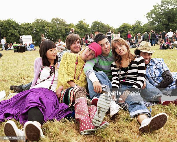 Group of friends sitting on grass by crowd, portrait
