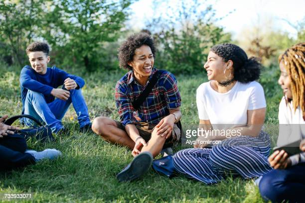 group of friends sitting on grass, laughing - teenagers only stock pictures, royalty-free photos & images