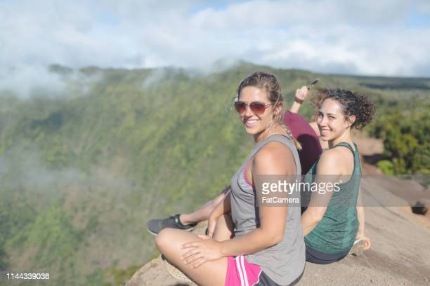 group of friends sitting on hawaii cliff overlooking valley - waimea valley stock photos and pictures
