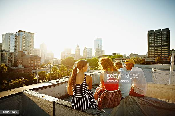 group of friends sitting on roof at sunset - s'évader du réel photos et images de collection