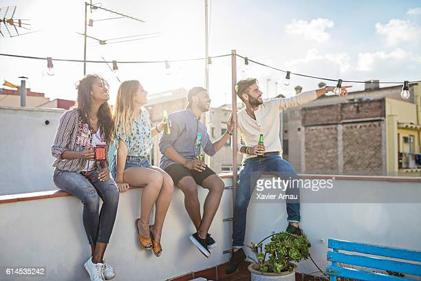 Group of friends sitting on rooftop with drinks