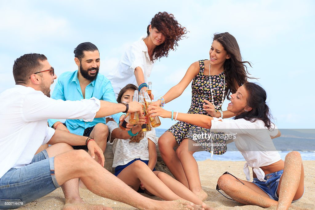 Gruppo di amici seduto su sabbia e celebrazione : Foto stock