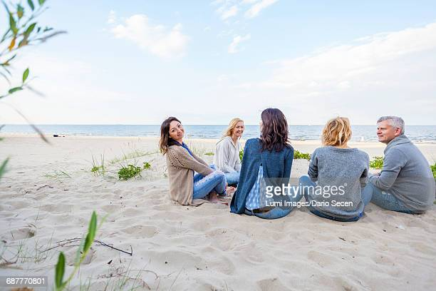 Group of friends sitting on sandy beach