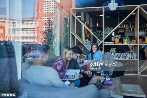 group of friends sitting together in a cafe with reflection of glass pane - kolonie stockfoto's en -beelden