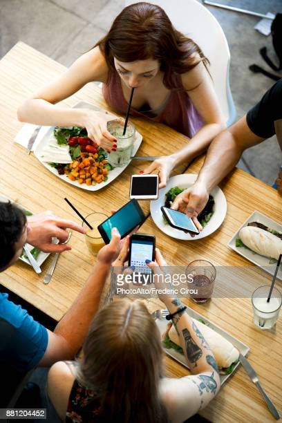 Group of friends sitting together in restaurants, all looking at smartphones