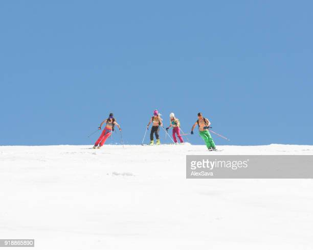 Group of friends skiing downhill snow-capped slope