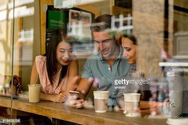 Group of friends social networking at a cafe