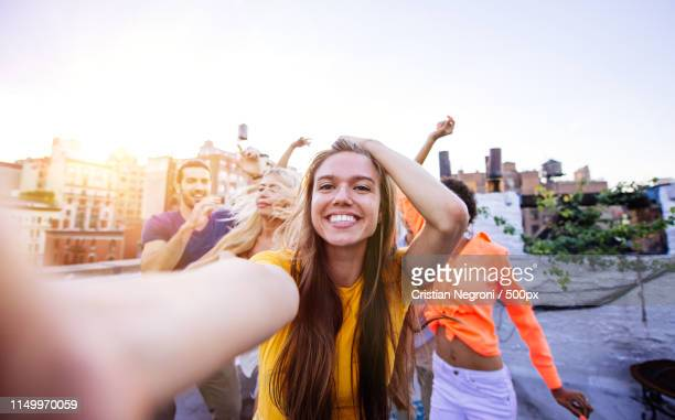 group of friends spending time together on a rooftop in new york - new yorker building stock photos and pictures