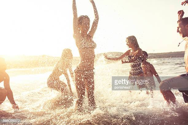 Group of friends splashing water in the sea