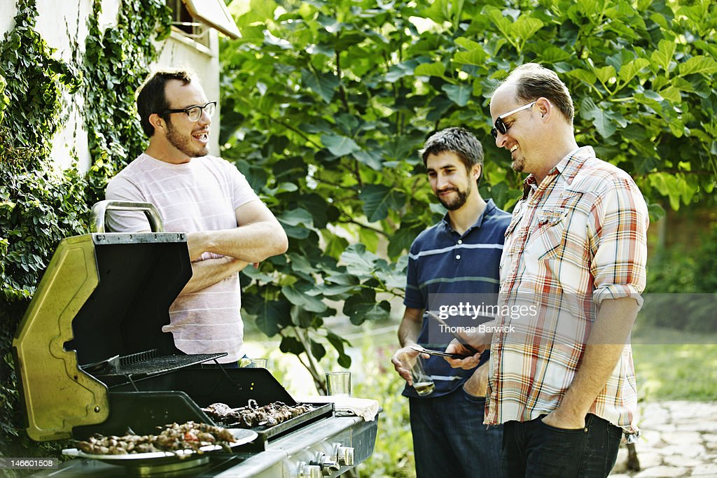 Group of friends standing around while barbecuing : Stock Photo