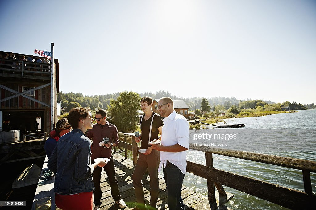 Group of friends standing eating on dock in sun : Stock Photo