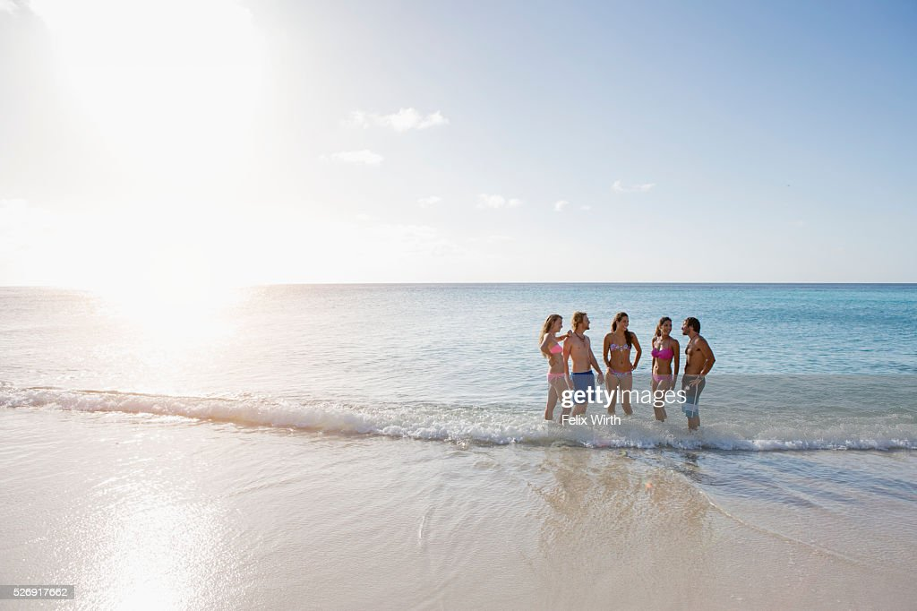 Group of friends standing together in shallow surf on beach : Stock Photo