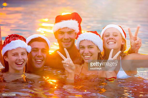 Group of friends swimming with Santa hats.