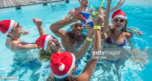 Group Of Friends Swimming With Santa Hats