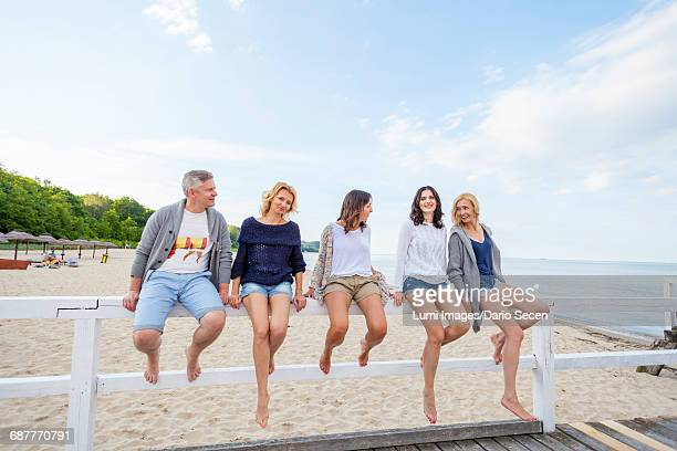 Group of friends take a break sitting on railing