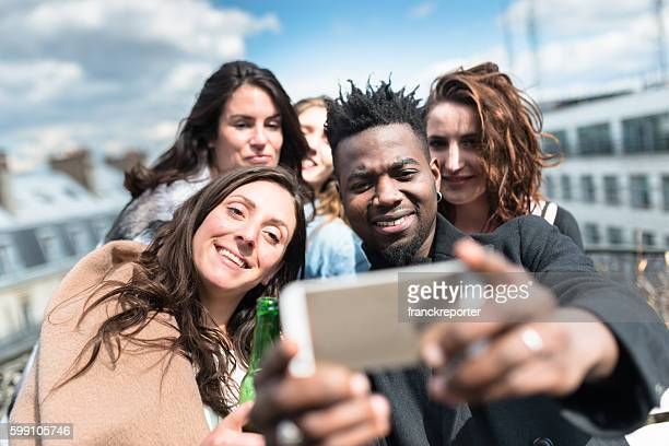 group of friends take a selfie on rooftop in paris