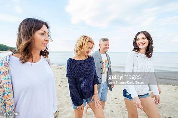 Group of friends take a walk along the beach