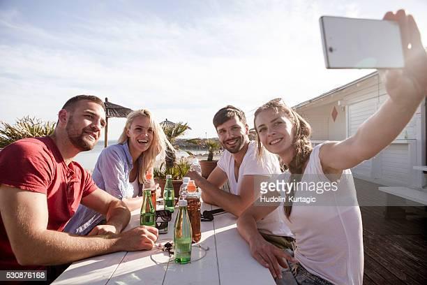 Group of friends taking a self portrait in beach bar