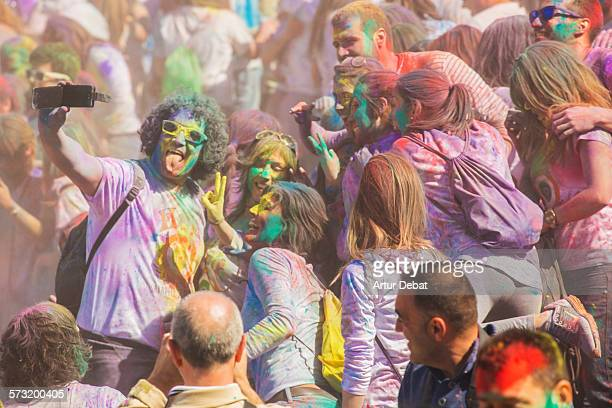 Group of friends taking a selfie with smartphone on the colorful Holi celebration