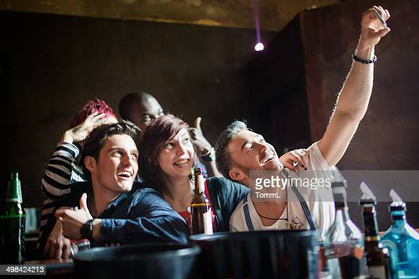 Group Of Friends Taking Photograph At Bar