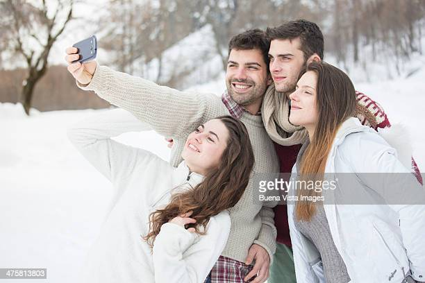 Group of friends taking pictures in  snow