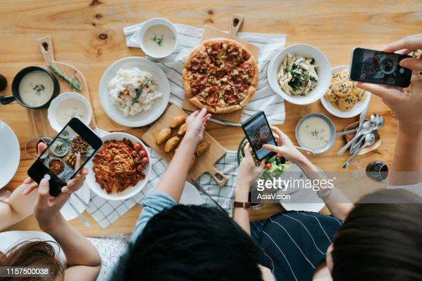 group of friends taking pictures of food on the table with smartphones during party - influencer stock pictures, royalty-free photos & images
