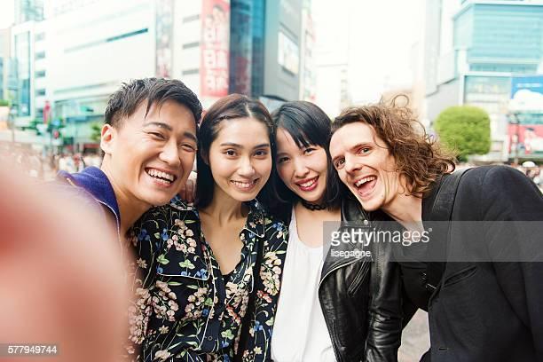 友人のグループセルフィを撮っている渋谷 - 混血 ストックフォトと画像