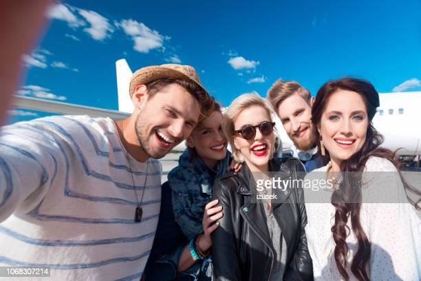 gruppo di amici che si fanno selfie in aeroporto - cinque persone foto e immagini stock