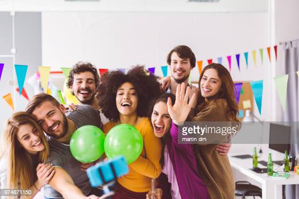 Group of friends taking selfie on office party