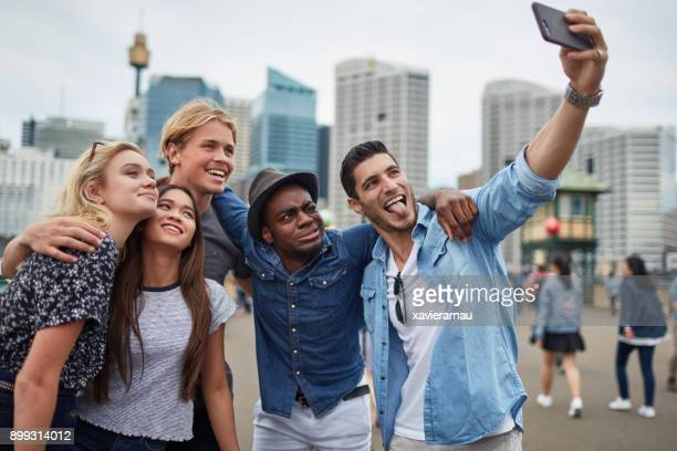 Group of friends taking selfie on smart phone