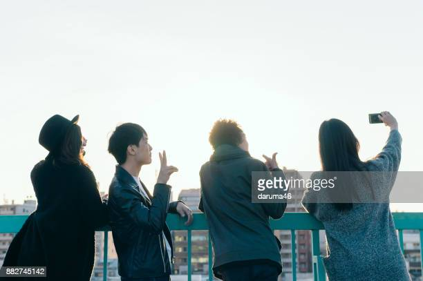 group of friends taking selfie on urban rooftop - generation z stock photos and pictures