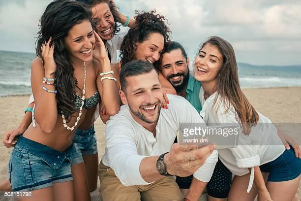 セルフィーを取るのグループご友人に電話ビーチで