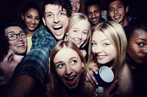 Group of friends taking selfies at a party - gettyimageskorea