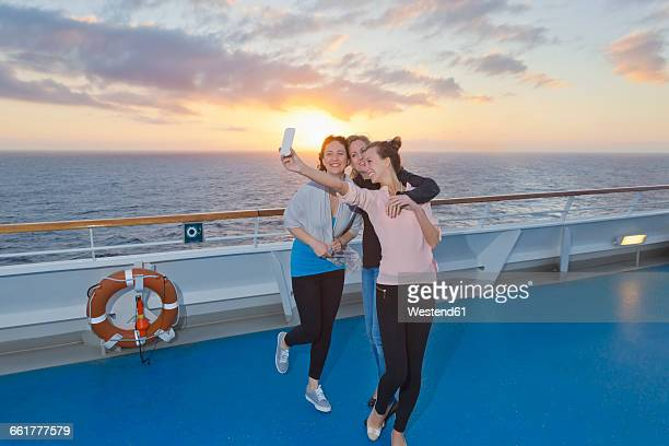 Group of friends taking selfies on a cruise