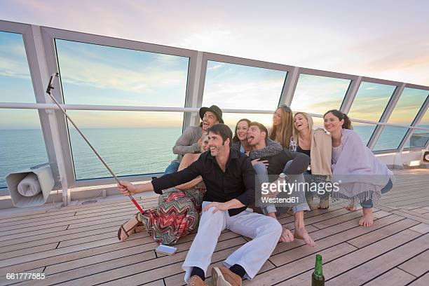 group of friends taking selfies on a cruise - passagier wasserfahrzeug stock-fotos und bilder