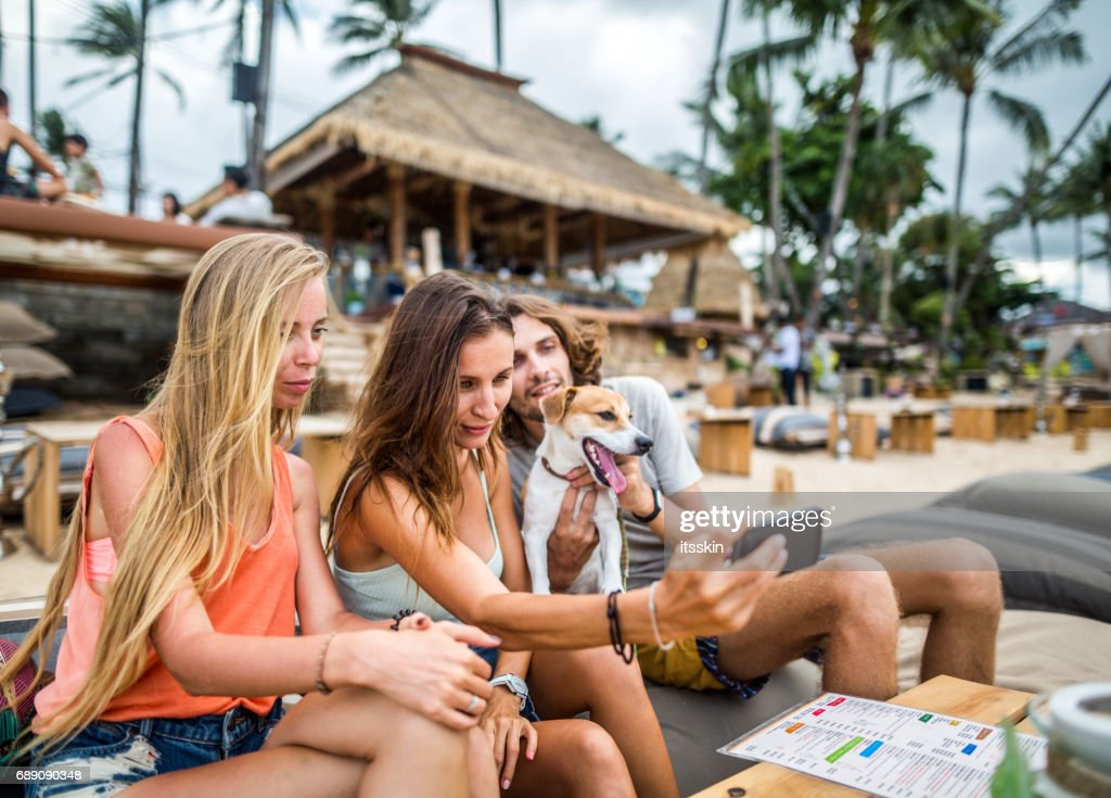 Group of friends taking selfies - two girls, one guy  and a cute dog with them at the beach cafe : Stock Photo