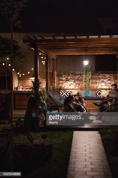 Group of friends talking and drinking beer in pergola