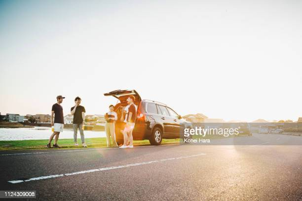 group of friends talking and getting relaxed by car outdoors - land vehicle stock pictures, royalty-free photos & images
