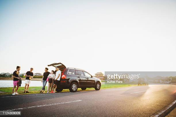 group of friends talking and getting relaxed by car outdoors - モータービークル ストックフォトと画像