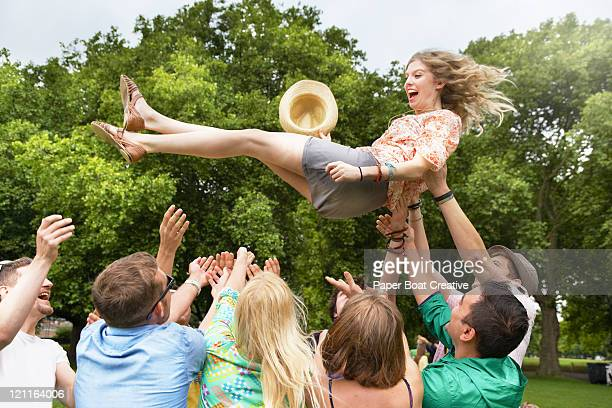 group of friends throwing a girl up in the air