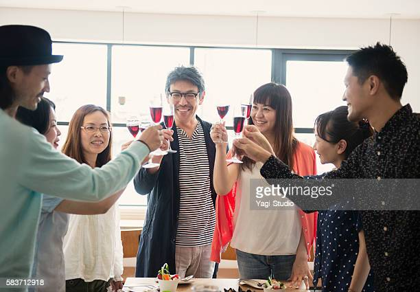 group of friends toasting at a guest house - パーティー ストックフォトと画像