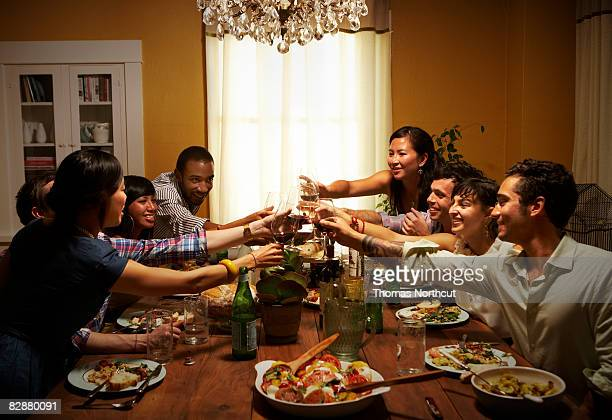 Group of friends toasting at dinner table