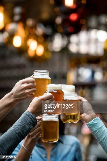 group of friends toasting at the bar - vertical stock pictures, royalty-free photos & images