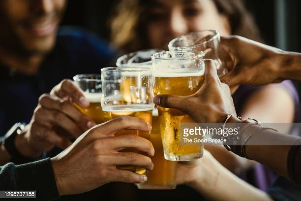 group of friends toasting beer glasses at table in bar - honour stock pictures, royalty-free photos & images
